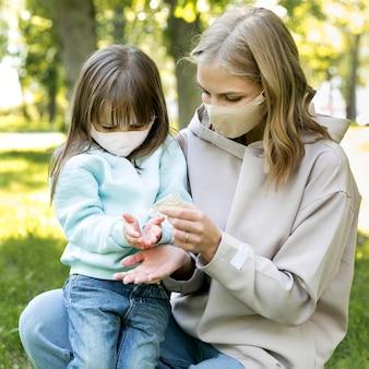 Jeune à l'extérieur et maman à l'aide d'un désinfectant pour les mains