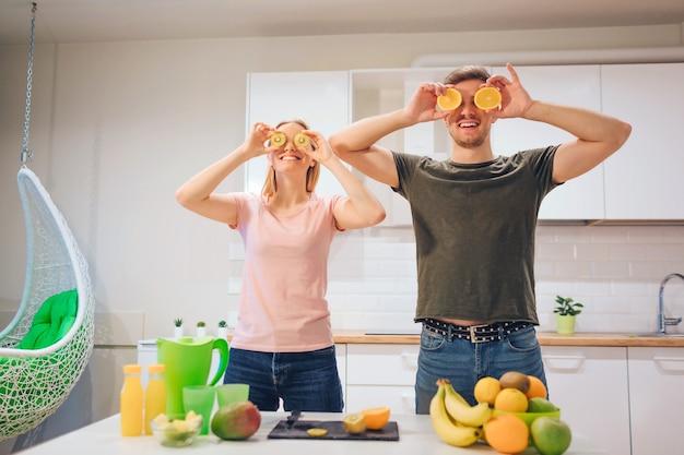 Jeune famille aimante s'amuse avec l'orange biologique tout en cuisinant ensemble des fruits frais dans une cuisine blanche