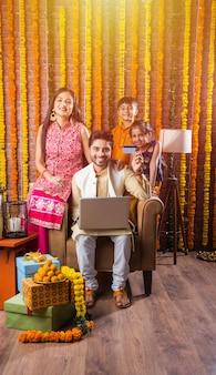 Jeune famille asiatique indienne faisant du shopping en ligne le soir du festival de diwali avec carte électronique et ordinateur portable