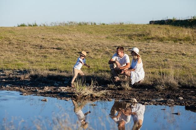 Une jeune famille au bord de l'étang regarde leur reflet