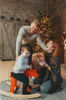 Jeune, famille, caucasien, famille, papa, fils, près, cheminée, arbre noël