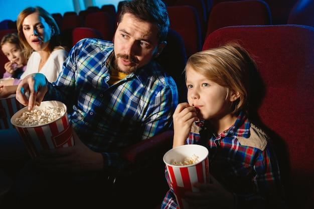 Jeune famille caucasienne regardant un film dans un cinéma, une maison ou un cinéma. ayez l'air expressif, étonné et émotif. s'asseoir seul et s'amuser. relation, amour, famille, enfance, week-end.
