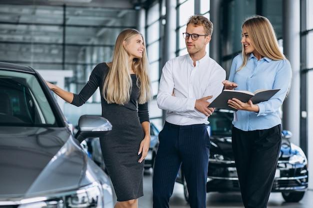 Jeune famille choisissant une voiture dans une salle d'exposition