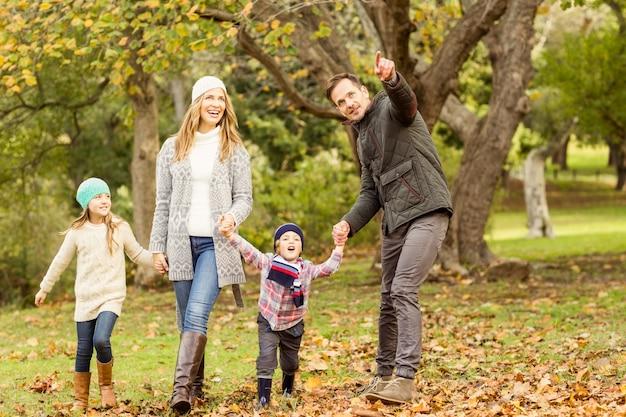 Jeune famille en cours d'exécution dans les feuilles