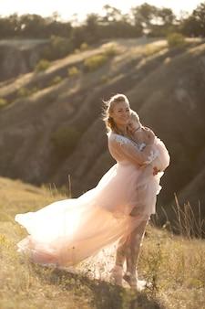 Une jeune famille dans la nature dans des robes identiques. belle jeune maman tient sa fille dans ses bras. champ et collines