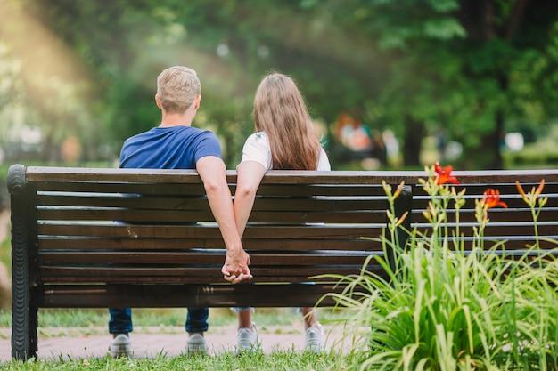 Jeune famille détendue sur le banc dans le parc