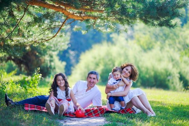 Jeune famille avec deux enfants assis sur l'herbe sous le pin.