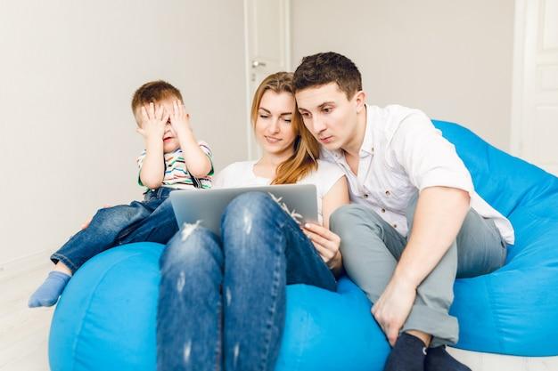 Jeune famille de deux parents et d'un enfant garçon assis sur des chaises bleues.