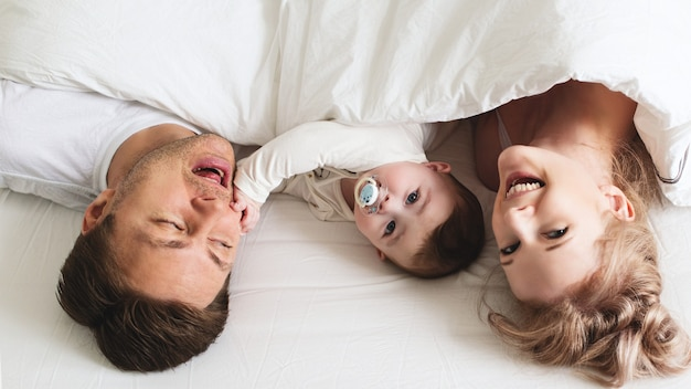 Jeune famille drôle avec bébé au lit, matin lifestyle