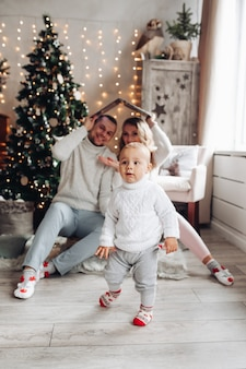 Jeune famille avec un enfant dans le salon décoré avec arbre de noël