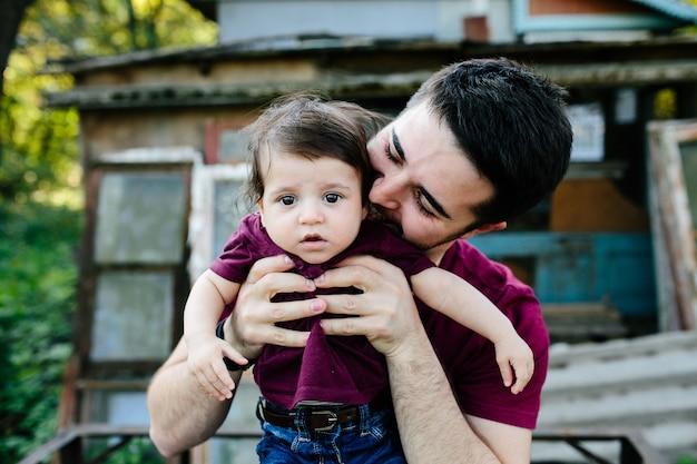 Jeune famille avec enfant posant sur un bâtiment abandonné