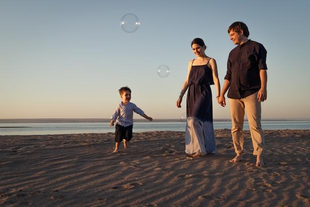 Une jeune famille avec un enfant se promène le long de la plage le soir, des bulles de savon à la lumière naturelle volent