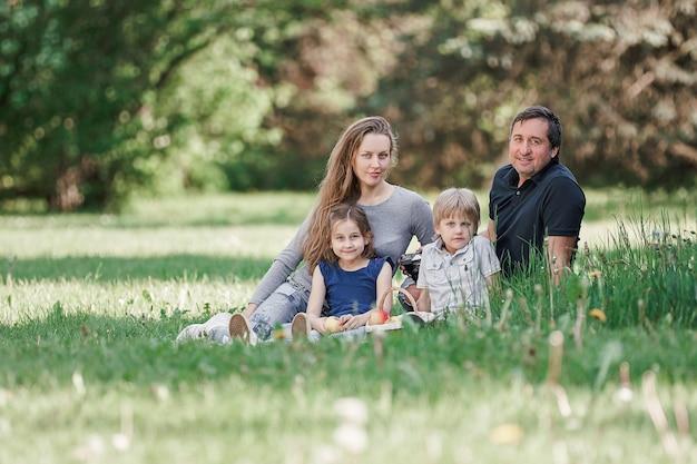 Jeune famille avec enfants assis sur la pelouse le jour de vesani