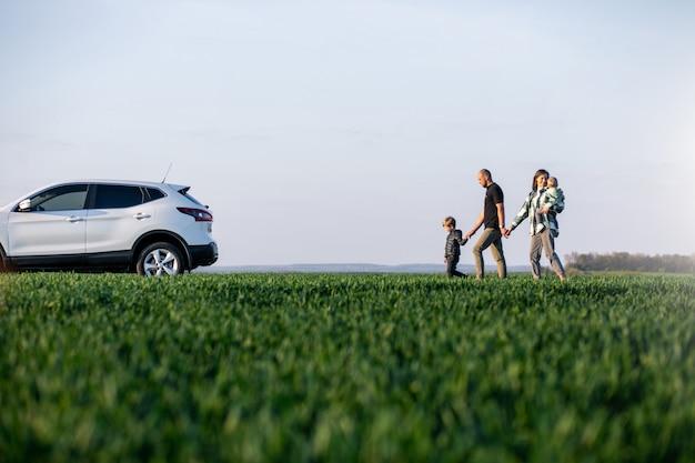 Jeune famille avec enfants voyageant en voiture, arrêtée sur le terrain