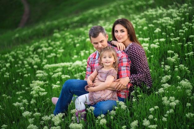 La jeune famille est assise sur l'herbe verte