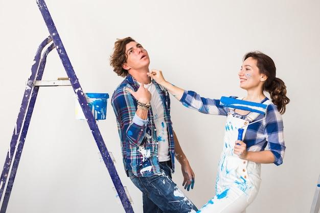 Jeune famille faisant la redécoration et la peinture des murs