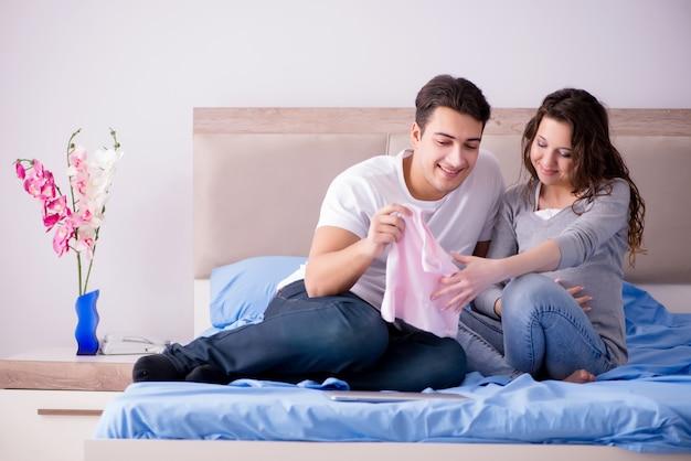 Jeune famille avec une femme enceinte attend son bébé au lit