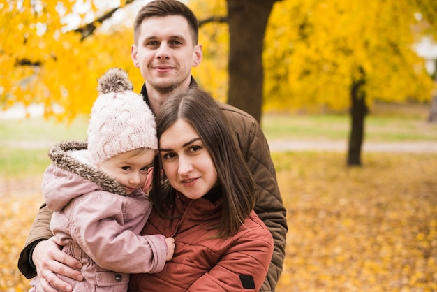 Jeune famille avec fille dans le parc avec des feuilles jaunes