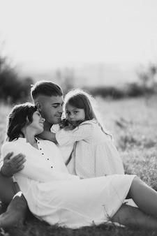 Jeune famille avec fille dans le pré
