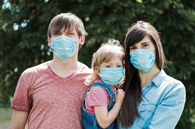Jeune famille avec fille portant des masques faciaux