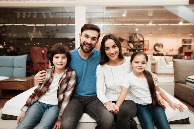 Jeune famille heureuse assis sur un matelas étreignant
