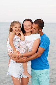Jeune famille heureuse au bord de la mer
