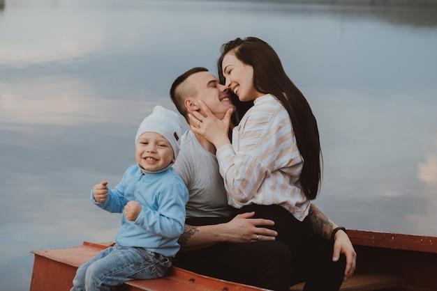 Jeune famille heureuse blanche avec leur fils s'asseoir dans un bateau au bord de l'eau en été