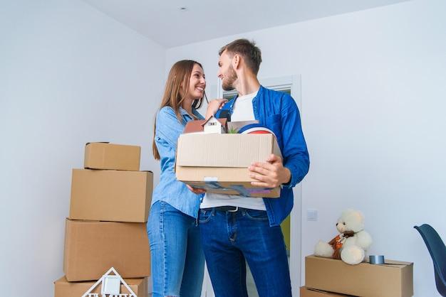 Jeune famille heureuse avec des boîtes en carton ouvrant la porte de leur nouvelle maison et entrant dans un appartement vide.