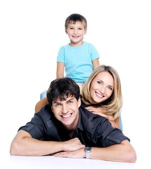 Jeune famille heureuse avec enfant posant sur un espace blanc