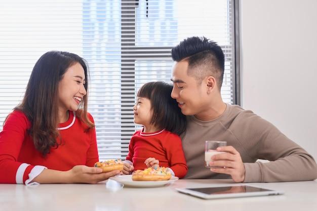 Jeune famille heureuse avec des enfants appréciant le petit déjeuner dans une salle à manger ensoleillée blanche avec une grande fenêtre de vue de jardin