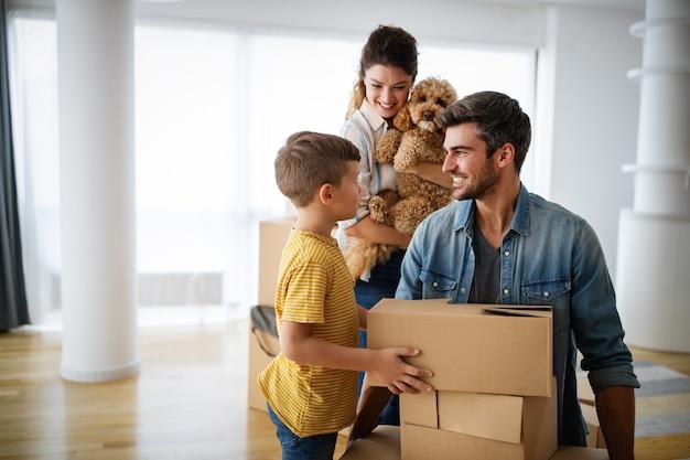 Jeune famille heureuse avec des enfants se déplaçant avec des boîtes dans un nouvel immeuble.