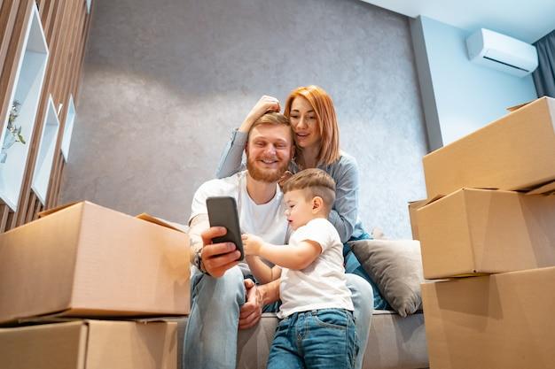 Jeune, famille heureuse, à, gosse, déballage, boîtes, ensemble, s'asseoir sofa