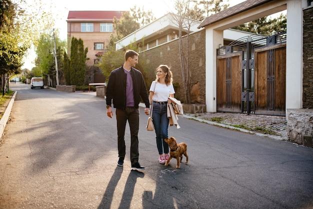 Une jeune famille heureuse, un homme et une femme amoureux s'amusent à marcher avec leur chien dans un parc d'automne dans la nature en automne en plein air, mise au point sélective