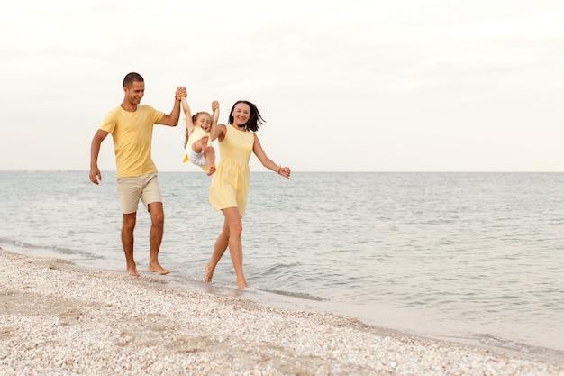 Jeune famille heureuse en jaune jouer avec leur enfant au bord de la mer