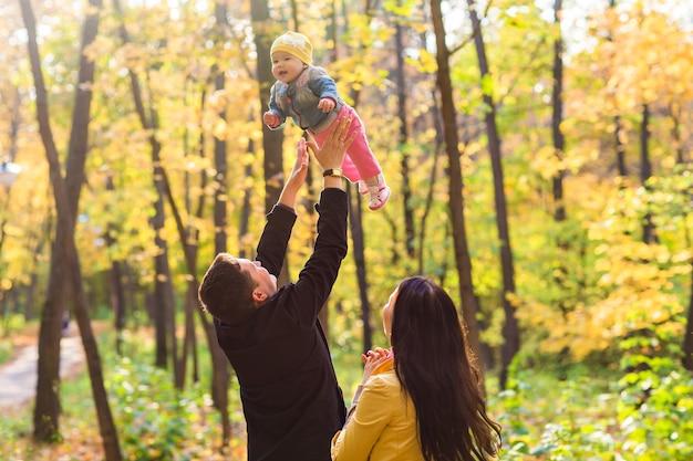 Jeune famille heureuse avec leur fille passant du temps en plein air dans le parc en automne.