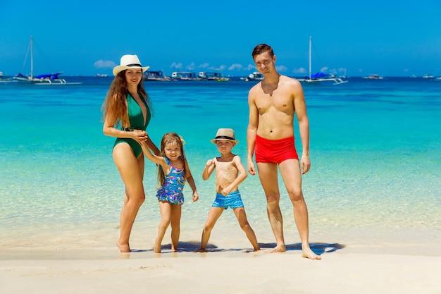 Jeune famille heureuse, maman, papa, fille et fils s'amusant sur une plage tropicale de sable. le concept de voyage et de vacances en famille.