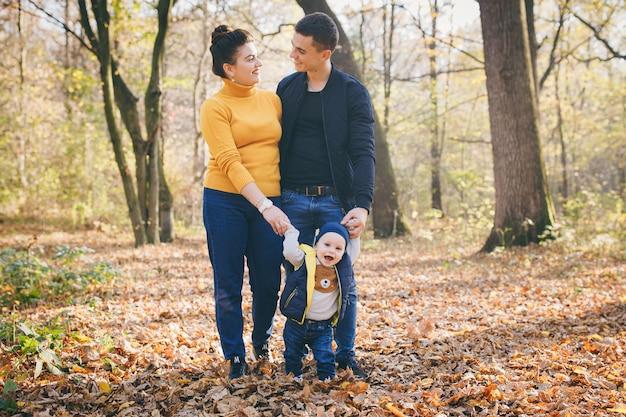 Jeune famille heureuse en marchant dans le parc en automne. la famille et leurs fils se promènent dans le parc d'automne et passent un bon moment.