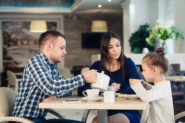 Jeune famille heureuse, parler dans un restaurant