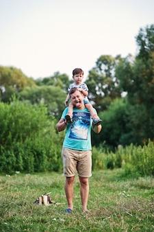 Jeune famille heureuse : père avec fils sur la nature s'amusant.