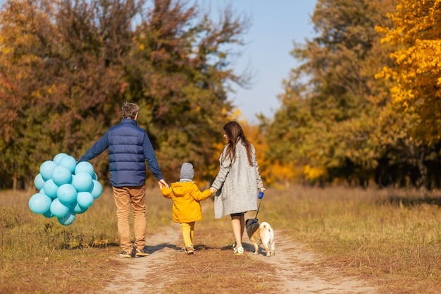 Une jeune famille heureuse avec un petit enfant et un chien passe du temps ensemble pour une promenade dans le parc en automne.