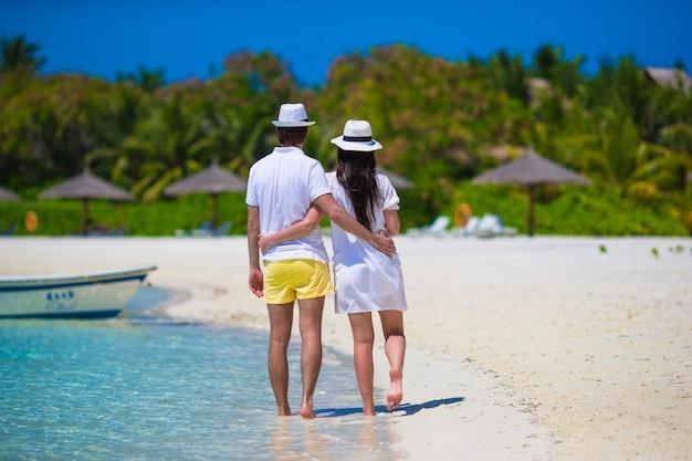 Jeune famille heureuse sur la plage blanche en vacances d'été