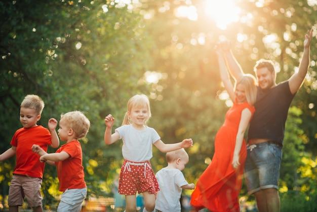 Jeune famille heureuse s'amuser dans le parc