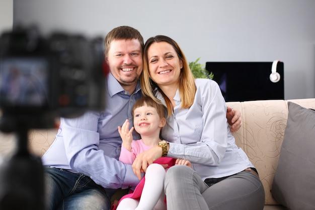 Jeune famille heureuse s'asseoir sur le canapé faisant portrait en séance photo