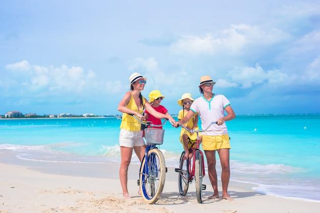 Jeune famille heureuse à vélo sur la plage tropicale