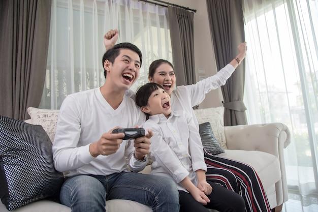 Jeune famille jouant à des jeux vidéo à la maison et s'amusant ensemble.