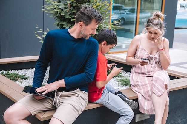 Une jeune famille joue à des jeux vidéo au téléphone. les parents et le fils passent du temps à l'air frais. photo de haute qualité.lifestyle