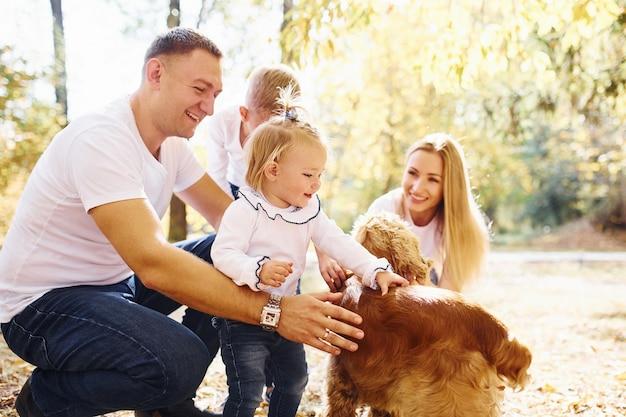 Une jeune famille joyeuse avec un chien se repose ensemble dans un parc en automne.