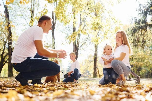 Une jeune famille joyeuse se repose ensemble dans un parc d'automne.