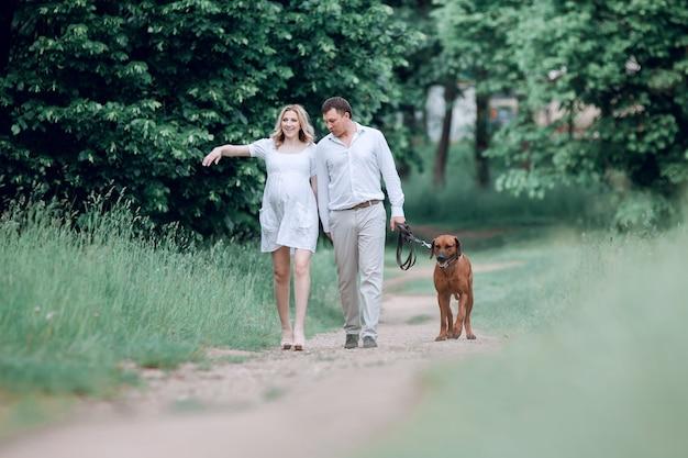 Jeune famille et leur animal de compagnie marchant le long du chemin dans le parc