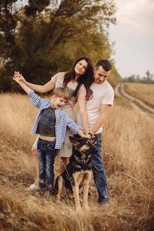 Jeune famille et leur chien passent du temps sur la nature l'après-midi d'automne